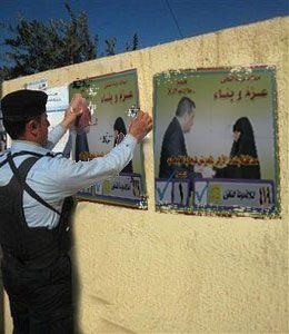 شرطي عراقي يترك واجبه الامني وينشغل بتعليق بوسترات الحملة الانتخابية لائتلاف دولة القانون!!