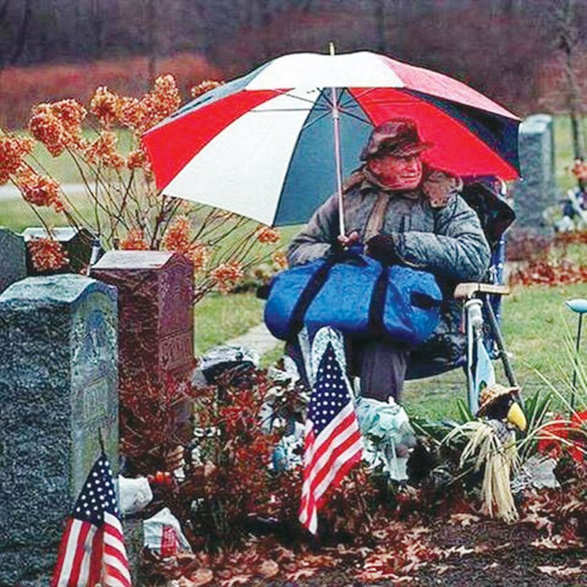 رجل يجلس بجوار قبر زوجته 20 عاماً