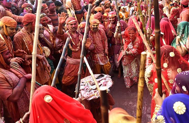 في مهرجان الألوان بالهند .. النساء يطاردن الرجال بالعصي